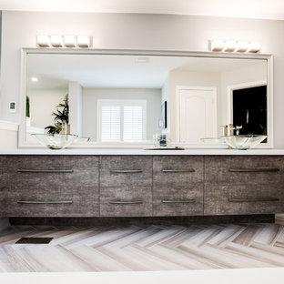 Idéer för ett mellanstort modernt en-suite badrum, med släta luckor, skåp i mellenmörkt trä, en dusch i en alkov, en toalettstol med hel cisternkåpa, grå kakel, keramikplattor, grå väggar, ett fristående handfat, bänkskiva i kvarts, dusch med gångjärnsdörr, ett platsbyggt badkar, laminatgolv och beiget golv