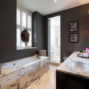 Modern inredning av ett badrum, med ett undermonterad handfat, ett undermonterat badkar, grå väggar och marmorgolv