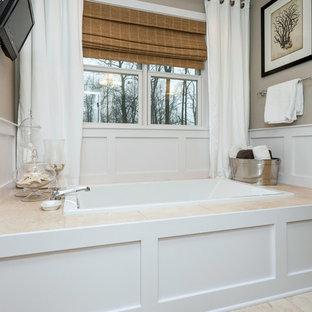 Ejemplo de cuarto de baño principal, de estilo americano, de tamaño medio, con lavabo bajoencimera, armarios con paneles lisos, puertas de armario blancas, encimera de granito, bañera encastrada, ducha empotrada, sanitario de una pieza, baldosas y/o azulejos beige, losas de piedra, paredes grises y suelo de travertino
