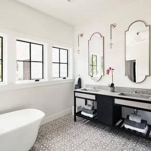 Modelo de cuarto de baño principal, tradicional renovado, grande, con puertas de armario negras, bañera exenta, baldosas y/o azulejos de cemento, suelo de azulejos de cemento, lavabo integrado y encimera de esteatita
