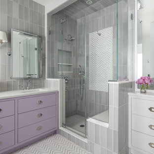 Modelo de cuarto de baño con ducha, tradicional renovado, con armarios con paneles lisos, puertas de armario violetas, ducha esquinera, baldosas y/o azulejos grises, paredes grises, lavabo bajoencimera, suelo multicolor, ducha con puerta con bisagras y encimeras blancas