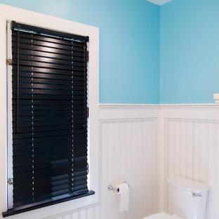 Cette image montre une grand salle de bain principale style shabby chic avec un placard à porte shaker, des portes de placard noires, une baignoire en alcôve, un combiné douche/baignoire, un carrelage noir et blanc, des carreaux de porcelaine, un mur bleu, un sol en carrelage de porcelaine, un lavabo intégré et un plan de toilette en quartz modifié.