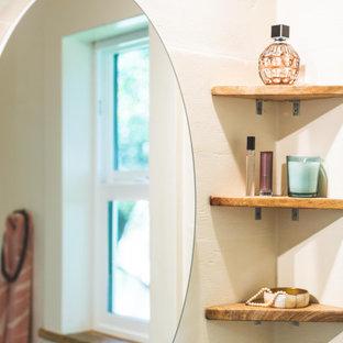 На фото: маленькая ванная комната в морском стиле с открытыми фасадами, светлыми деревянными фасадами, угловым душем, раздельным унитазом, синей плиткой, керамической плиткой, белыми стенами, полом из ламината, душевой кабиной, настольной раковиной, столешницей из дерева, коричневым полом, душем с раздвижными дверями, коричневой столешницей, нишей, тумбой под одну раковину, подвесной тумбой и сводчатым потолком