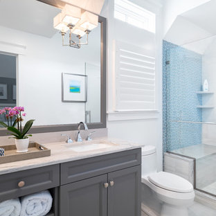 Bathroom - mid-sized coastal kids' blue tile and glass tile beige floor and marble floor bathroom idea in Philadelphia with recessed-panel cabinets, gray cabinets, a one-piece toilet, white walls, an undermount sink, marble countertops, a hinged shower door and beige countertops