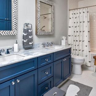 Cette image montre une grande salle de bain design pour enfant avec un placard à porte shaker, des portes de placard bleues, un carrelage blanc, un carrelage métro, un sol en carrelage de céramique, un plan de toilette en marbre, une baignoire en alcôve, un combiné douche/baignoire, un WC séparé, un mur gris et un lavabo encastré.