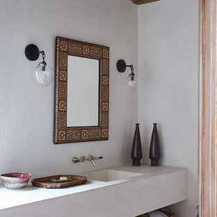 Example of a tuscan bathroom design in Santa Barbara with open cabinets, white walls, an integrated sink and white countertops
