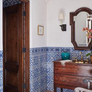 Design ideas for a mediterranean bathroom in Santa Barbara with freestanding cabinets, medium wood cabinets, blue tiles, white tiles, white walls, medium hardwood flooring, a submerged sink, wooden worktops, brown floors and brown worktops.