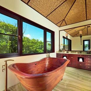 Modelo de cuarto de baño principal, asiático, grande, con lavabo bajoencimera, armarios con paneles empotrados, puertas de armario de madera oscura, encimera de ónix, bañera exenta, combinación de ducha y bañera, baldosas y/o azulejos verdes, losas de piedra y paredes beige