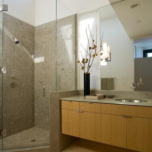 Imagen de cuarto de baño minimalista, de tamaño medio, con lavabo bajoencimera, armarios con paneles lisos, puertas de armario de madera oscura, ducha esquinera, baldosas y/o azulejos de piedra, paredes blancas, suelo de bambú, encimera de vidrio y baldosas y/o azulejos grises
