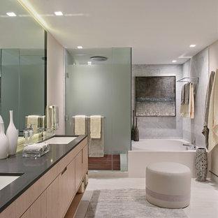 Modernes Badezimmer mit flächenbündigen Schrankfronten, hellen Holzschränken, Eckbadewanne, Eckdusche, grauen Fliesen, beiger Wandfarbe, Unterbauwaschbecken, beigem Boden, Falttür-Duschabtrennung und schwarzer Waschtischplatte in Miami