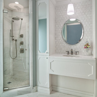 Inspiration for a large contemporary master bathroom in Miami with an undermount sink, white cabinets, a corner shower, white tile, white walls, recessed-panel cabinets, marble, marble floors, marble benchtops, white floor, a hinged shower door and white benchtops.