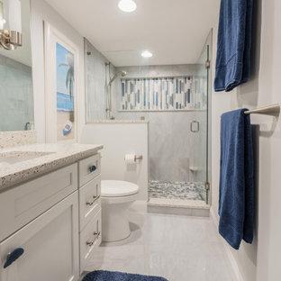 Пример оригинального дизайна: главная ванная комната среднего размера в морском стиле с фасадами с утопленной филенкой, белыми фасадами, душем в нише, серой плиткой, керамогранитной плиткой, серыми стенами, полом из керамогранита, врезной раковиной, столешницей из переработанного стекла, серым полом, душем с распашными дверями и белой столешницей