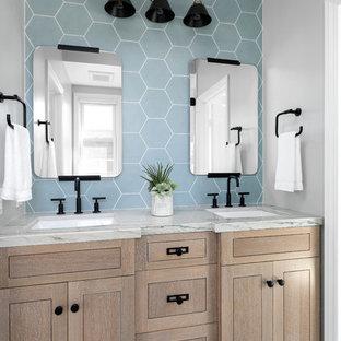 オレンジカウンティのビーチスタイルのおしゃれな子供用バスルーム (家具調キャビネット、淡色木目調キャビネット、青いタイル、グレーの壁、アンダーカウンター洗面器、グレーの床、グレーの洗面カウンター) の写真