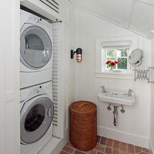 Cette photo montre une salle de bain bord de mer avec un mur blanc, un sol en brique, un lavabo suspendu et buanderie.
