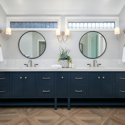 Inspiration for a coastal master brown floor bathroom remodel in Orange County with furniture-like cabinets, blue cabinets, gray walls, an undermount sink and white countertops
