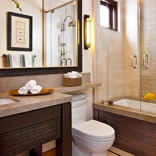 Пример оригинального дизайна: ванная комната среднего размера в современном стиле с врезной раковиной, открытыми фасадами, темными деревянными фасадами, ванной в нише, душем над ванной, бежевой плиткой, столешницей из известняка, унитазом-моноблоком, бежевыми стенами, полом из известняка и плиткой из известняка