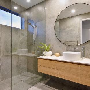 Modelo de cuarto de baño costero con armarios con paneles lisos, puertas de armario de madera oscura, ducha a ras de suelo, baldosas y/o azulejos grises, lavabo sobreencimera, suelo gris y ducha abierta