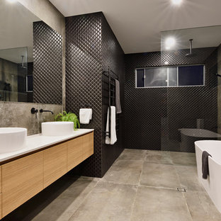 This is an example of a mid-sized contemporary 3/4 bathroom in Sunshine Coast with brown cabinets, cement tiles, a vessel sink, grey floor, an open shower, a freestanding tub, an open shower and black tile.