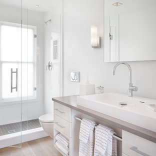 Alcove shower - large beach style white tile medium tone wood floor alcove shower idea in Boston with a vessel sink, flat-panel cabinets, white cabinets, white walls and gray countertops