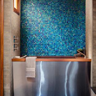 Ispirazione per una stanza da bagno minimal con vasca giapponese, piastrelle blu, piastrelle a mosaico e pareti beige