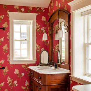 Immagine di una grande stanza da bagno con doccia tradizionale con ante a filo, ante in legno bruno, piastrelle beige, piastrelle in gres porcellanato, pareti rosse, pavimento in gres porcellanato, lavabo da incasso e top in marmo
