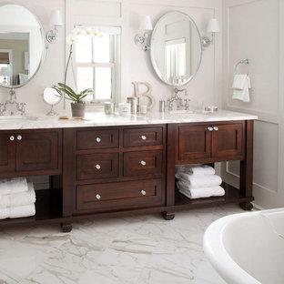 Foto på ett mellanstort funkis en-suite badrum, med ett undermonterad handfat, möbel-liknande, skåp i mörkt trä, vita väggar, marmorgolv, vitt golv, ett fristående badkar och marmorbänkskiva