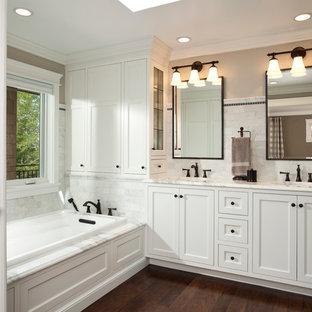 Idée de décoration pour une salle de bain principale tradition de taille moyenne avec un placard avec porte à panneau encastré, des portes de placard blanches, une baignoire posée, un carrelage blanc, un mur beige, un sol en bois foncé, du carrelage en marbre, un lavabo encastré, un plan de toilette en marbre et un sol marron.
