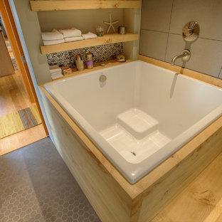 Immagine di una grande stanza da bagno padronale etnica con vasca giapponese, piastrelle grigie, piastrelle in gres porcellanato, pareti grigie e pavimento in gres porcellanato