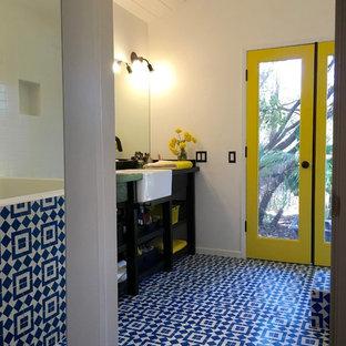 Foto de cuarto de baño principal, bohemio, de tamaño medio, con armarios abiertos, puertas de armario negras, baldosas y/o azulejos azules, baldosas y/o azulejos blancos, baldosas y/o azulejos en mosaico, encimera de madera, bañera japonesa, paredes blancas, suelo con mosaicos de baldosas y lavabo encastrado