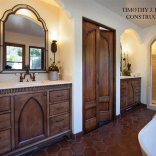 Réalisation d'une petit salle de bain principale méditerranéenne avec un placard en trompe-l'oeil, des portes de placard en bois vieilli, une baignoire indépendante, une douche d'angle, un carrelage blanc, des carreaux de céramique, un mur blanc, un sol en carreau de terre cuite, un lavabo encastré, un plan de toilette en calcaire, un sol marron et une cabine de douche à porte battante.