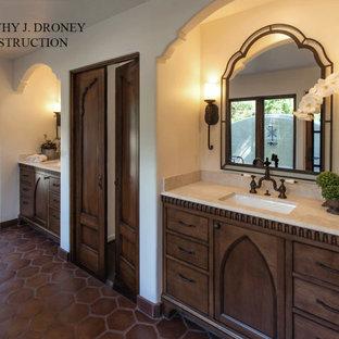 Inspiration pour une petit salle de bain principale méditerranéenne avec un placard en trompe-l'oeil, des portes de placard en bois vieilli, une baignoire indépendante, une douche d'angle, un carrelage blanc, des carreaux de céramique, un mur blanc, un sol en carreau de terre cuite, un lavabo encastré, un plan de toilette en calcaire, un sol marron, une cabine de douche à porte battante et un plan de toilette beige.
