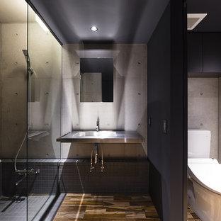 Immagine di una stanza da bagno minimal con vasca ad angolo, doccia aperta, piastrelle grigie, pareti grigie, parquet scuro, lavabo a consolle, top in acciaio inossidabile, pavimento marrone e doccia aperta