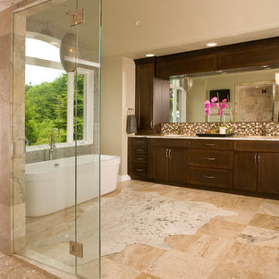 Bathroom - large transitional master beige tile and travertine tile travertine floor and beige floor bathroom idea in Seattle with shaker cabinets, dark wood cabinets, a two-piece toilet, beige walls, an undermount sink, granite countertops, a hinged shower door and multicolored countertops