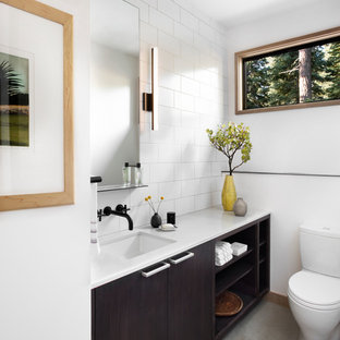 Example of a large trendy 3/4 white tile and subway tile porcelain floor bathroom design in San Francisco with flat-panel cabinets, dark wood cabinets, white walls, an undermount sink, solid surface countertops and a one-piece toilet
