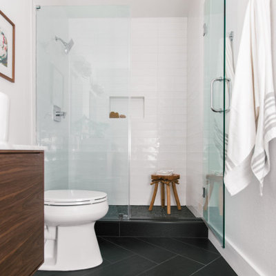 Example of a small danish master white tile and subway tile ceramic tile, black floor and double-sink alcove shower design in Tampa with flat-panel cabinets, brown cabinets, a one-piece toilet, white walls, a vessel sink, quartz countertops, a hinged shower door, white countertops and a freestanding vanity