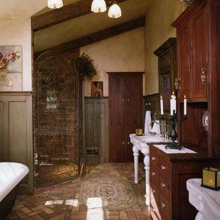 Esempio di una stanza da bagno stile rurale con vasca con piedi a zampa di leone, lavabo a consolle e pavimento in mattoni