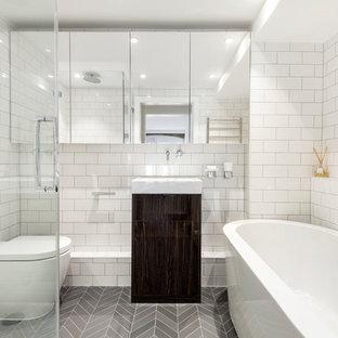 Cette photo montre une salle de bain tendance de taille moyenne avec un placard à porte plane, des portes de placard marrons, une baignoire indépendante, une douche à l'italienne, un WC à poser, un carrelage métro, un mur blanc, sol en stratifié, un plan vasque, un sol gris et une cabine de douche à porte battante.