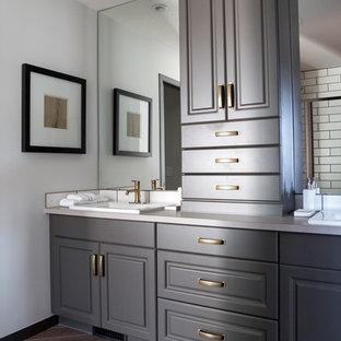 カルガリーの小さいトラディショナルスタイルのおしゃれなマスターバスルーム (レイズドパネル扉のキャビネット、グレーのキャビネット、アルコーブ型シャワー、分離型トイレ、白いタイル、セラミックタイル、白い壁、磁器タイルの床、オーバーカウンターシンク、ラミネートカウンター) の写真