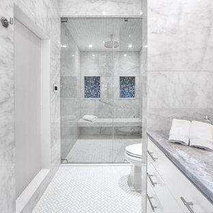 Inspiration för ett mycket stort tropiskt blå blått en-suite badrum, med släta luckor, blå skåp, ett fristående badkar, en toalettstol med hel cisternkåpa, vit kakel, marmorkakel, vita väggar, marmorgolv, ett nedsänkt handfat, marmorbänkskiva, vitt golv och dusch med gångjärnsdörr