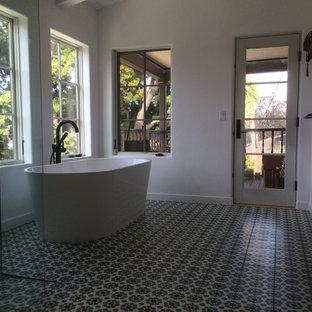 サンディエゴの広いラスティックスタイルのおしゃれなマスターバスルーム (フラットパネル扉のキャビネット、ヴィンテージ仕上げキャビネット、置き型浴槽、コーナー設置型シャワー、一体型トイレ、白い壁、モザイクタイル、ベッセル式洗面器、人工大理石カウンター) の写真
