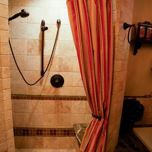 Foto di una stanza da bagno mediterranea di medie dimensioni con top in granito, vasca da incasso, doccia alcova, piastrelle beige, piastrelle in pietra, pareti beige, pavimento in travertino, ante con bugna sagomata, ante verdi, WC a due pezzi e lavabo sottopiano