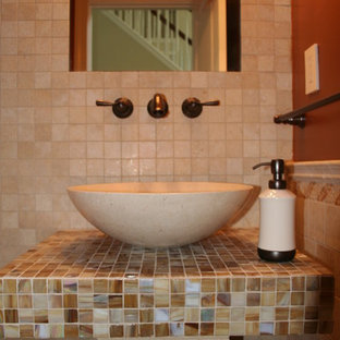Bathroom - small mediterranean 3/4 beige tile and ceramic tile bathroom idea in DC Metro with orange walls, a vessel sink and tile countertops