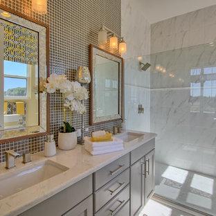 Esempio di una stanza da bagno padronale mediterranea di medie dimensioni con pareti beige, pavimento in gres porcellanato, ante in stile shaker, ante grigie, doccia alcova, piastrelle grigie, lastra di vetro, lavabo sottopiano, top in quarzo composito, pavimento grigio e porta doccia scorrevole