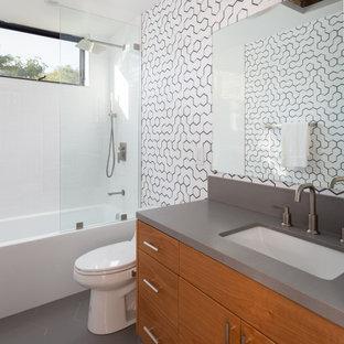 Modelo de cuarto de baño con ducha, actual, con armarios con paneles lisos, puertas de armario de madera oscura, bañera empotrada, combinación de ducha y bañera, baldosas y/o azulejos blancas y negros, lavabo bajoencimera, suelo gris, ducha abierta y encimeras grises