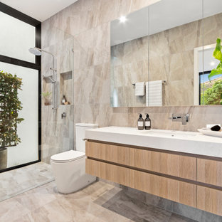 Design ideas for a contemporary master bathroom in Melbourne with flat-panel cabinets, light wood cabinets, a curbless shower, a two-piece toilet, beige tile, beige walls, an undermount sink, beige floor, an open shower, white benchtops, a niche and a floating vanity.