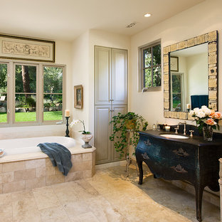 Tuscan beige tile and travertine tile drop-in bathtub photo in Santa Barbara with furniture-like cabinets and black cabinets