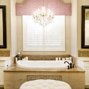 Bild på ett mellanstort vintage en-suite badrum, med vita skåp, ett platsbyggt badkar, beige kakel, luckor med upphöjd panel, stenkakel, beige väggar, marmorgolv och marmorbänkskiva
