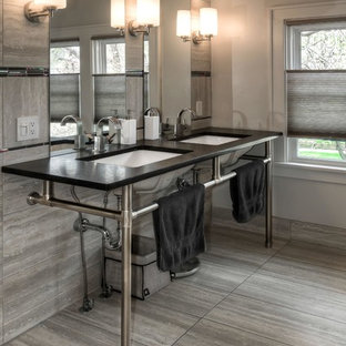 Design ideas for a medium sized contemporary ensuite bathroom in Omaha with a submerged sink, grey tiles, porcelain tiles, grey walls, porcelain flooring, soapstone worktops, grey floors and freestanding cabinets.