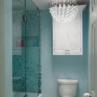 Modelo de cuarto de baño infantil, bohemio, de tamaño medio, con lavabo sobreencimera, armarios con paneles con relieve, puertas de armario blancas, encimera de cuarzo compacto, bañera empotrada, ducha empotrada, sanitario de una pieza, baldosas y/o azulejos azules, baldosas y/o azulejos en mosaico, paredes azules, suelo de baldosas de porcelana, suelo beige, ducha con puerta con bisagras y encimeras blancas