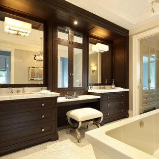 Ispirazione per una grande stanza da bagno chic con ante a filo, ante in legno bruno, vasca freestanding, doccia aperta, WC monopezzo, piastrelle bianche, piastrelle in pietra, pareti grigie, pavimento in marmo, lavabo sottopiano e top in marmo